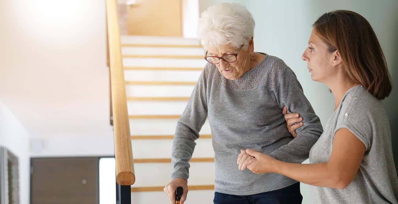 Senior with cane and caregiver